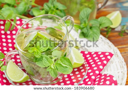 Mint and lime iced green tea.  Transparent cup of ice green tea with fresh  mint leaves and lime slices on table. Macro, selective focus - stock photo