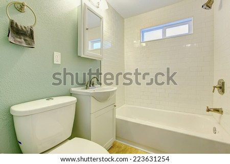Mint bathroom interior with white tile wall trim, white bath tub, washbasin cabinet and toilet - stock photo