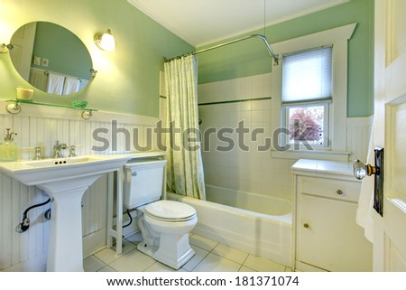 Mint bathroom with light green curtains, tile floor and wood plank wall trim. View of sink, toilet and bath tub - stock photo