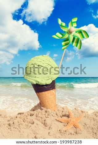 Mint icecream in chocolate wafer cone on the beach - vintage tone effect added - stock photo