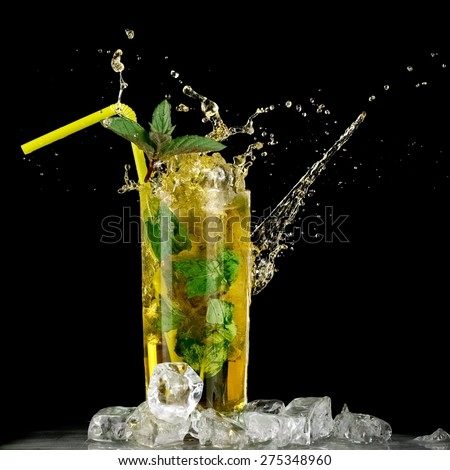 Mint julep splash on black background - stock photo