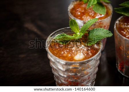 Mint Juleps in Decorative Silver Glasses on a dark reflective wood background with fresh sprigs of mint  - stock photo