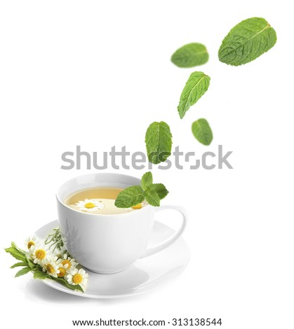 Mint leaves falling in cup of herbal tea, isolated on white - stock photo