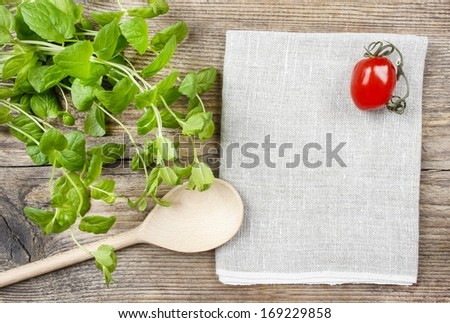 Mint leaves, wooden spoon and tomatoes on wooden table