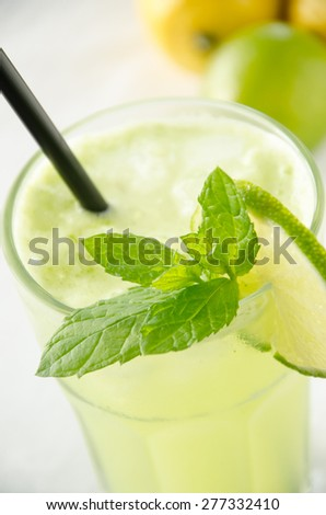 Mint, lemon and lime lemonade in a glass with black straw