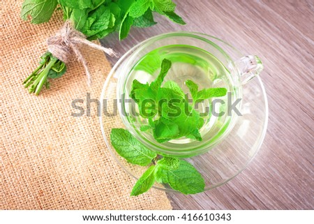 Mint tea in a transparent glass cup on the table