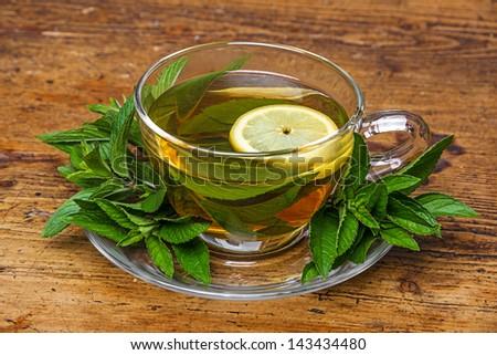mint tea on old wooden table - stock photo