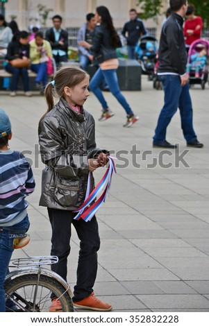 Mirny, Russia - June 12, 2014: Children with ribbons and flags in celebration of the Day of Russia in the city of Mirny, Republic of Sakha
