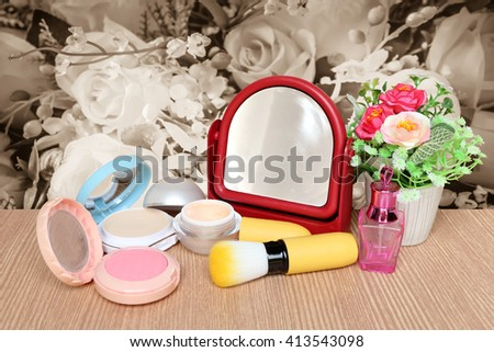 mirror and cosmetic tool with blur bunch of fabric roses background