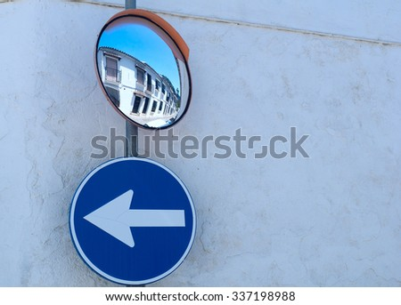Mirror and the road sign on the wall - stock photo