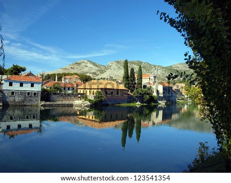 Mirror image of the old buildings in the town of Trebinje, Bosnia and Herzegovina in the water of the river. - stock photo