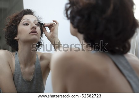 Mirror image of woman applying mascara
