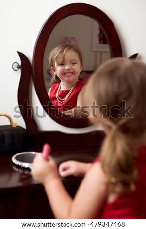 Mirror, Mirror.  Adorable preschooler looking in a mirror and putting on make up.
