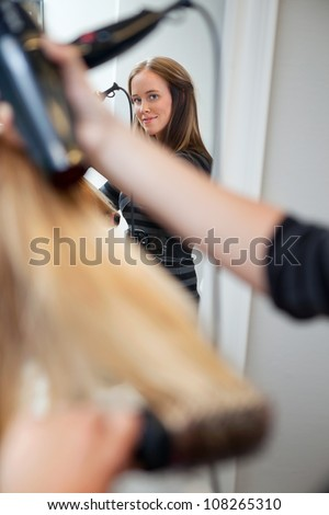 Mirror reflection of a beautiful professional hair stylist holding blow dryer - stock photo