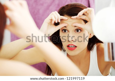 Mirror reflection of a woman worrying because of wrinkles on her forehead.