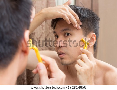 Mirror reflection of a young asian handsome man shaving - stock photo
