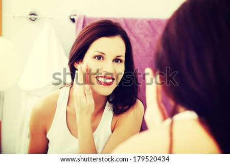 Mirror reflection of a young woman reapplying her face in the bathroom.