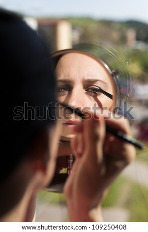mirror reflection of beautiful woman applying eyeliner. Caucasian woman holding hand mirror getting ready for her day putting makeup on eyes using natural light from outside going through the window. - stock photo