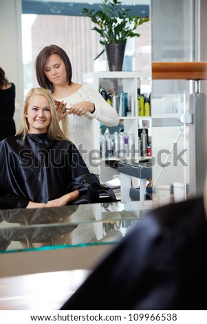 Mirror reflection of hairdresser giving young woman a new haircut at parlor - stock photo
