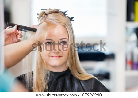 Mirror reflection of young woman getting her hair combed before haircut at parlor