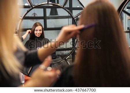 Mirror reflection of young woman getting her hairdo by stylist at parlor - stock photo