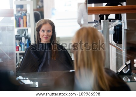 Mirror reflection of young woman smiling while sitting in parlor