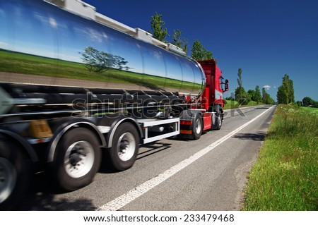 Mirroring the landscape chrome tank truck moving on a highway, view from eye level - stock photo
