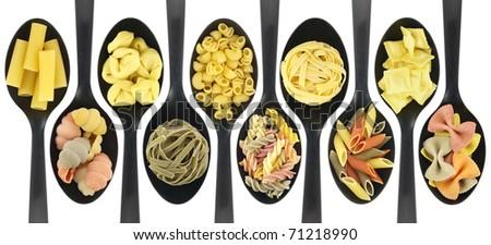 Misc raw pasta over spoons - stock photo
