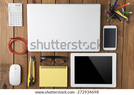 Miscellaneous office material on wood background, directly above shot - stock photo