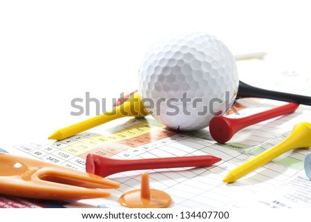 Miscellaneous parts used for playing golf: A ball, different colored tees, score card, a pitch fork and a ball marker. Studio shot, shallow depth of field.