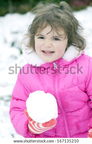 Mischievous little girl with a snowball - stock photo