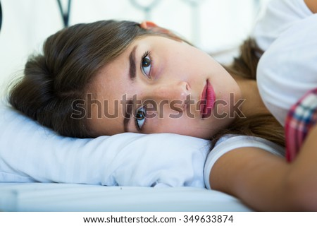 Miserable teenage girl with hanging look staying in bed - stock photo
