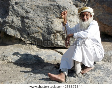 MISFA, OMAN - DEC 29 2007:An old Omani man wearing dishdash in Al Abreyeen village Misfah, Oman.It's an insight of how the locals used to live centuries ago. - stock photo