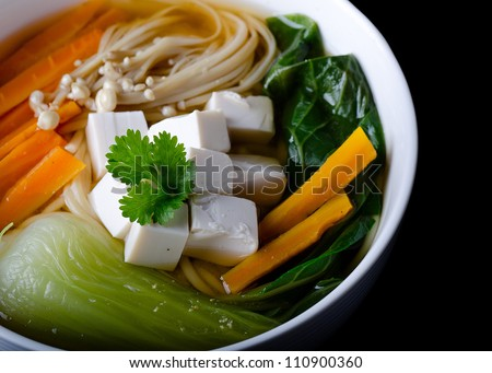 Miso soup with noodles, tofu, enoki and bok choy in a bowl - stock photo