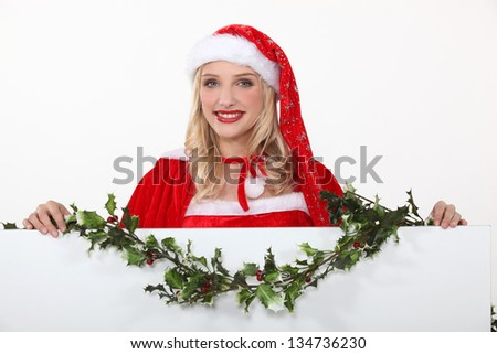 Miss Santa with a board left blank for your message - stock photo