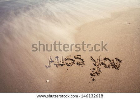 Miss you handwriting sign on sea sand with wave. Neutral densitiy filter used to make blurry waves. - stock photo