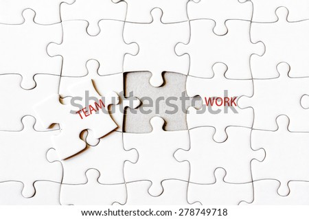 Missing jigsaw puzzle piece completing word TEAMWORK. Business concept image for completing the final puzzle piece. - stock photo
