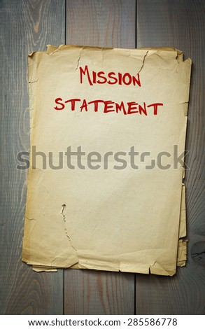 Mission statement. Old paper on a wooden background - stock photo