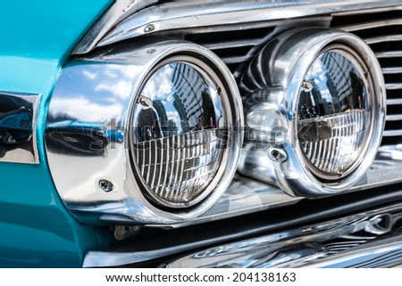 "MISSISSAUGA, CANADA - JULY 6 2014: A classic blue Ford Galaxie 500 headlamp or headlight. As seen at ""Classics on the Square"", a car show at Celebration Square in Mississauga, Canada on July 6, 2014."