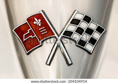 "MISSISSAUGA, CANADA - JULY 6 2014: Front hood emblem on a classic silver Chevrolet Corvette Stingray. 1965 or 1966 model. Seen at ""Classics on the Square"", a car show in Mississauga, Canada. - stock photo"