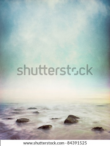 Mist and fog rising from a rocky ocean shore.  This image has a vintage paper texture and displays a pleasing grain pattern at 100%.