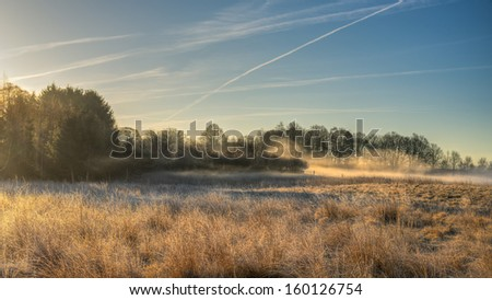 Mist is gathered on a meadow covered in hoar frost and early April morning. - stock photo