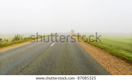 Mist on a country road. - stock photo