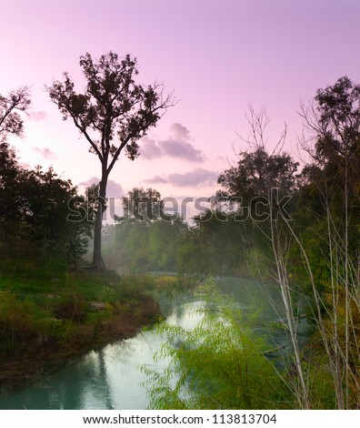 Mist rising from the San Marcos River in Texas at dawn. - stock photo