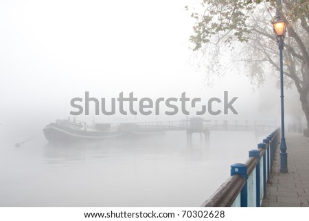 Mist shrouded jetty on river with streetlight - stock photo