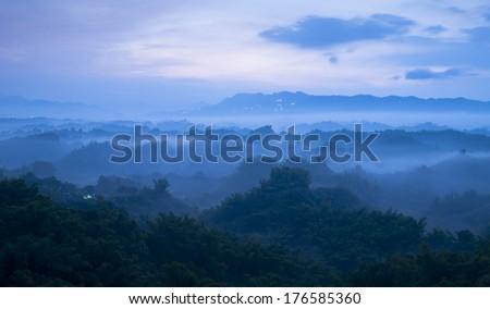 Mist-shrouded mountains with sunrise - stock photo