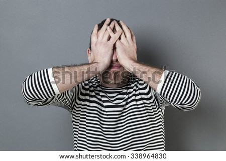 mistake concept - disturbed middle age man with striped sweater hiding his face for blindness expressing regret and disappointment - stock photo