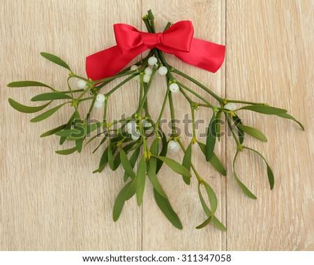 Mistletoe with red ribbon bow over light oak wood background. - stock photo