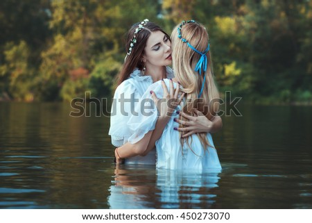 Mistresses women hugging, they dressed in white and standing in the water.