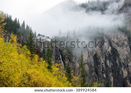 Misty Autumn at Bridal Veil Falls - A side view of Bridal Veil Falls, the highest (365-ft) free falling waterfall in Colorado, on a rainy and foggy autumn day, as seen from Black Bear Pass trail. - stock photo